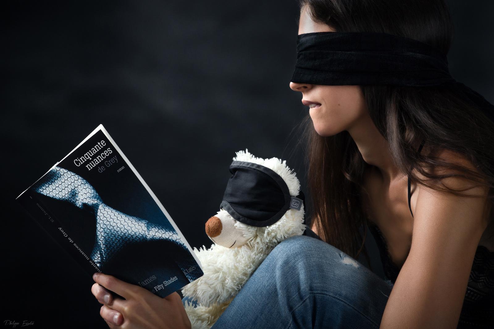 Un ours en peluche et un modèle photo, les yeux bandés, semblent apprécier le livre 50 Nuances de grey.