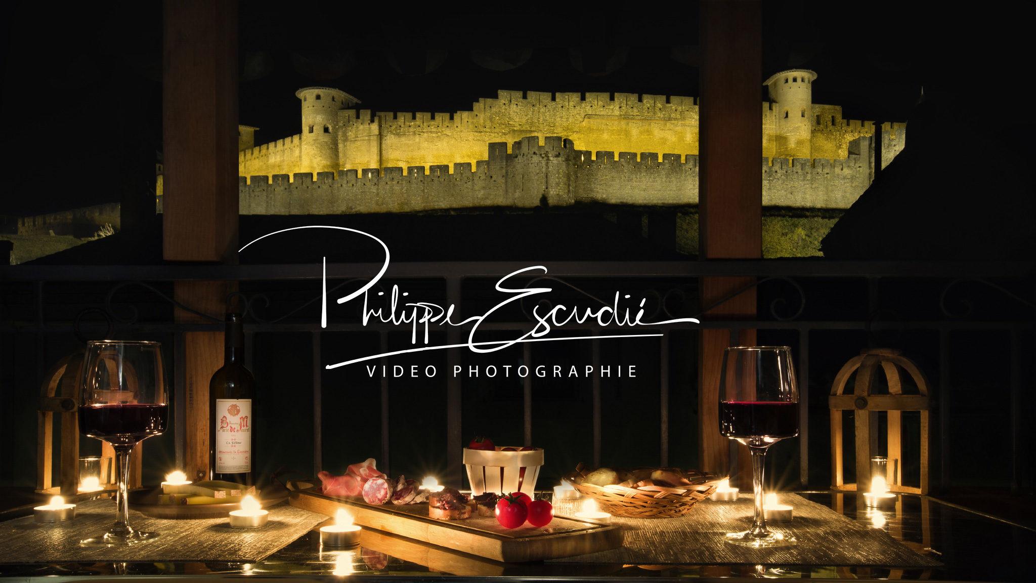 Ambiance apéritif de nuit sur une terrasse d'appartement, vin, charcuterie, bougie et la Cité de Carcassonne comme décor.