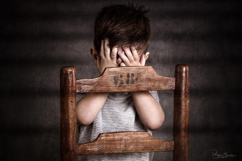 Enfant photographié en studio avec les mains se masquant le visage