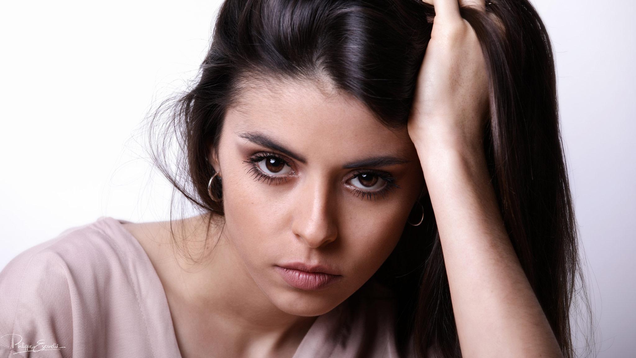 Portrait visage de Jennyfer, jeune modèle photo féminin, la main dans les cheveux.