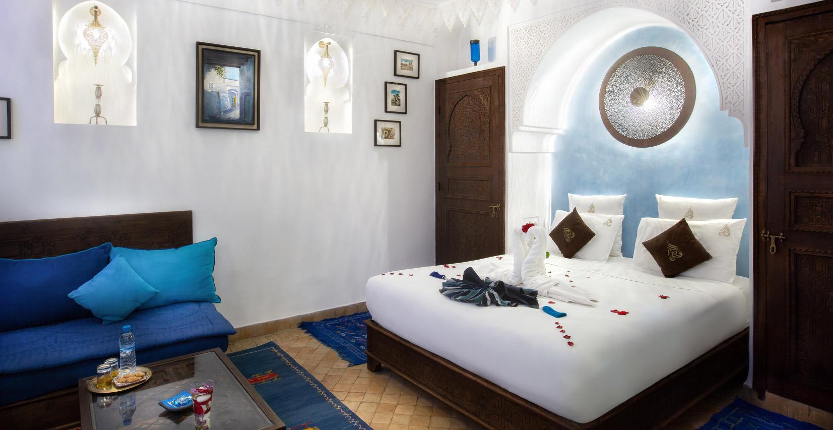 chambre de riad avec un grand lit sur lequel on voit deux serviettes pliées en forme d'oiseau et des pétales de roses tout autour