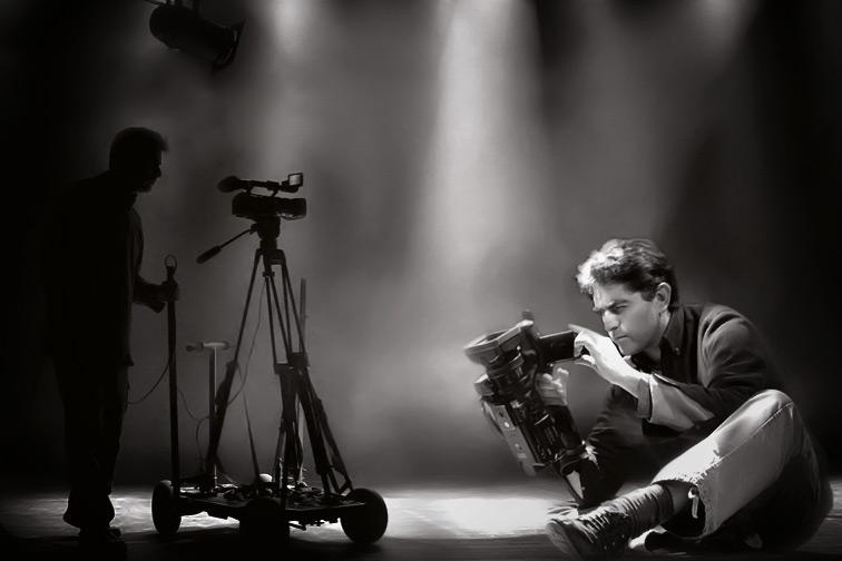Philippe Escudié est assis au premier plan, une caméra à la main et plus loin, debout, pousse un chariot de travelling