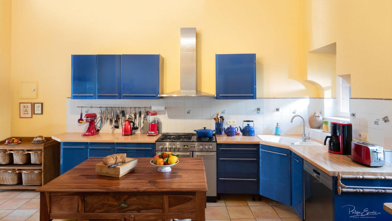 Cuisine de maison de maître, avec des placards bleus et une table en bois au premier plan sur laquelle reposent du pain et une corbeille de fruits.