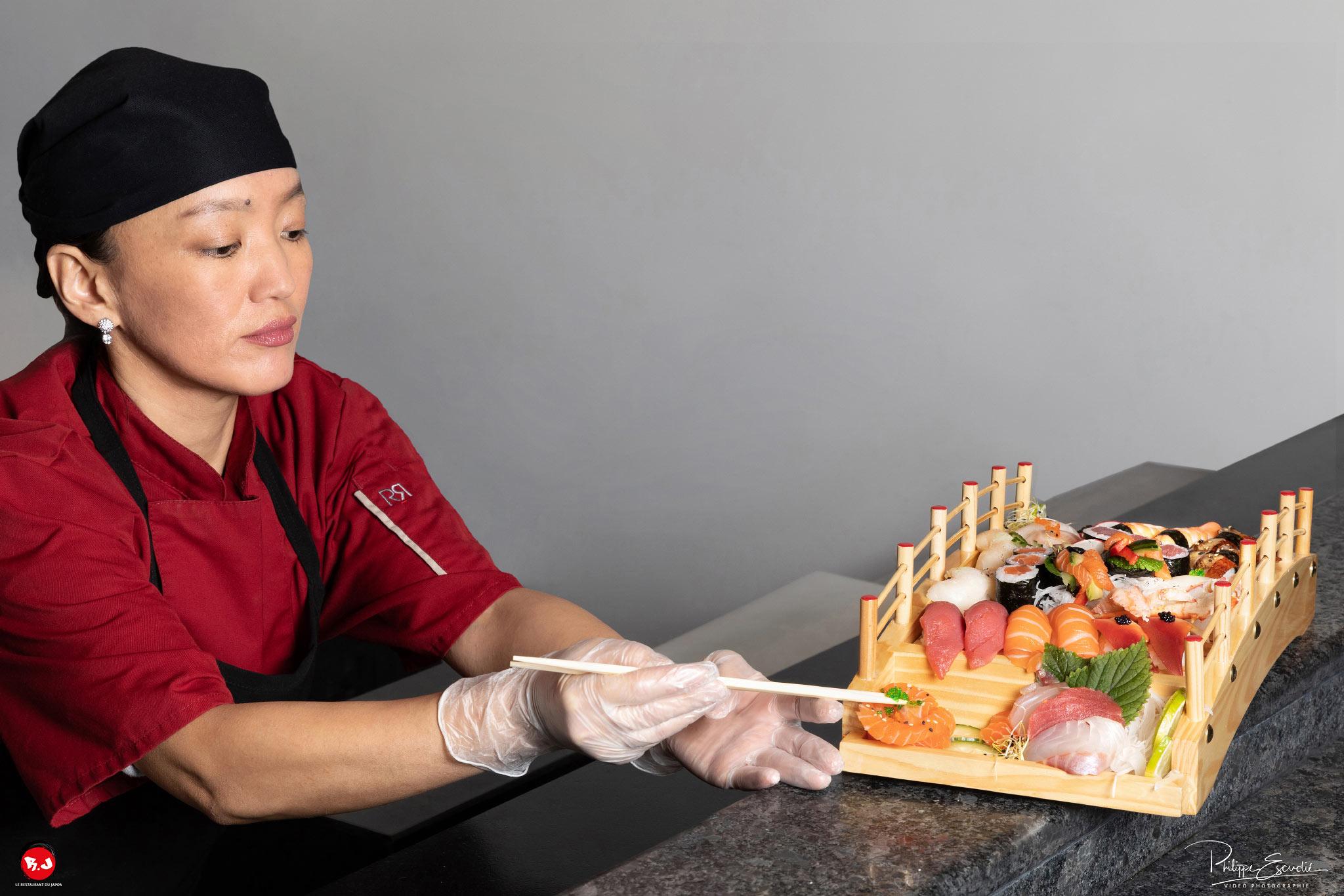 une chef cuisinière utilise des baguettes pour poser des oeufs de lompe sur un plat composé de sushis