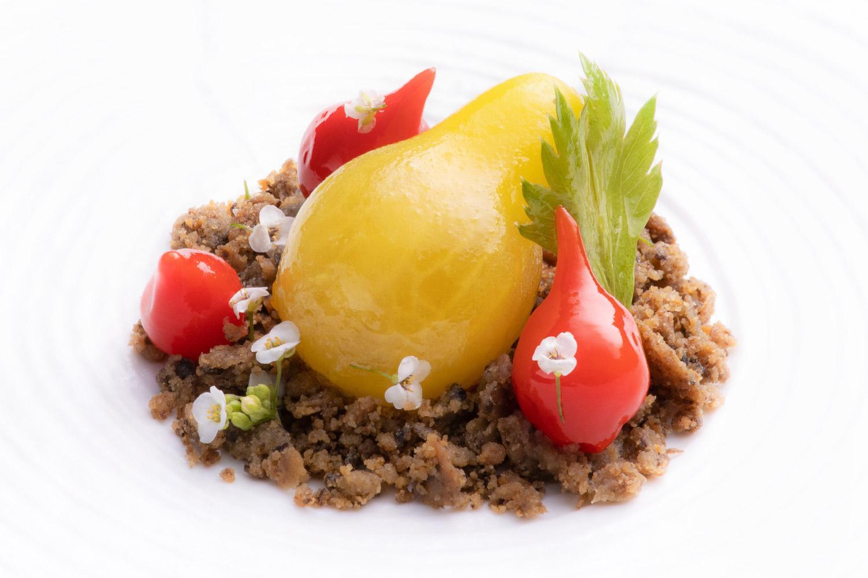 Trois mini tomates rouges et une tomate poire disposées dans une assiette sur un lit d'aubergine avec des petits fleurs blanches autour