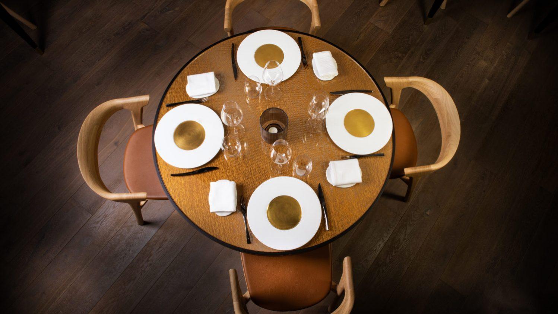 Quatre assiettes avec couverts sur une table ronde vue de dessus