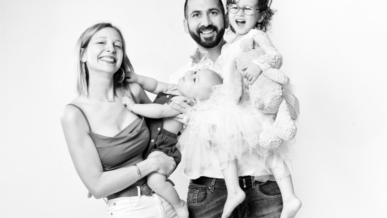 une famille composée d'un homme d'une femme d'une fillette et d'un bébé. Les parents tiennent chacun un enfant dans les bras.