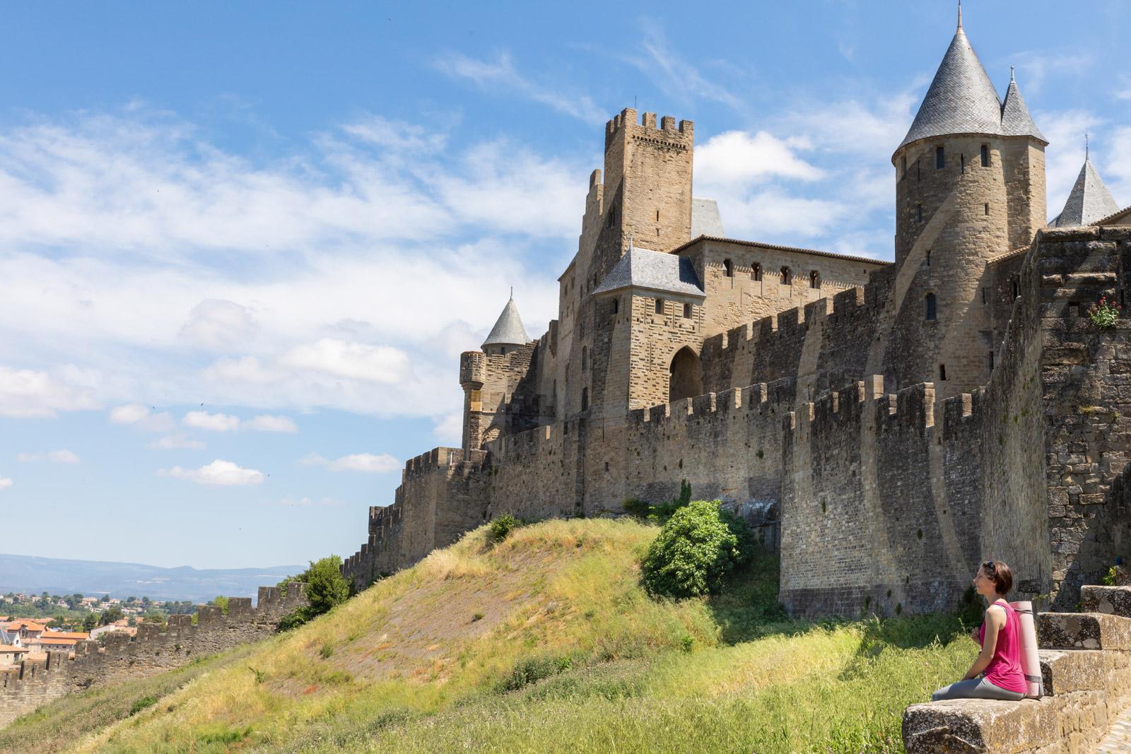 Une fille est assise devant les remparts d'une cité médiévale