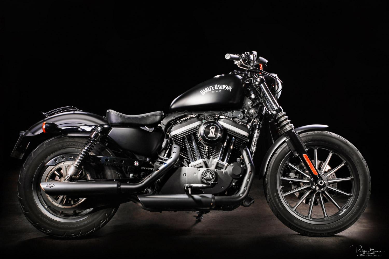 Une moto de marque Harley Davidson de profil sur fond noir